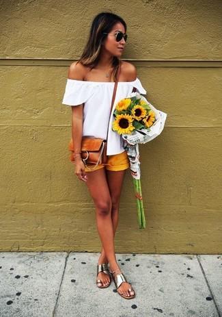 Cómo combinar: bolso bandolera de ante en tabaco, sandalias planas de cuero plateadas, pantalones cortos amarillos, top con hombros descubiertos blanco