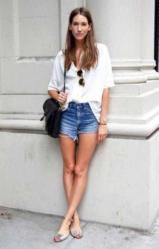 Cómo combinar: bolso bandolera de cuero negro, sandalias planas de cuero plateadas, pantalones cortos vaqueros azules, blusa de botones blanca