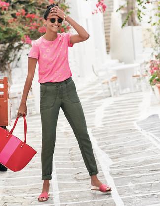 Cómo combinar: bolsa tote de cuero roja, sandalias planas de ante rosa, vaqueros verde oliva, camiseta con cuello circular estampada rosa