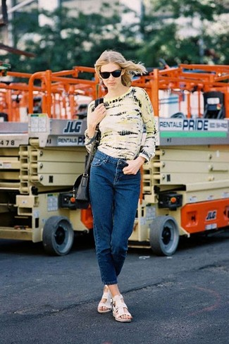 Cómo combinar: bolso bandolera de cuero negro, sandalias planas de cuero blancas, vaqueros azul marino, camiseta de manga larga efecto teñido anudado amarilla
