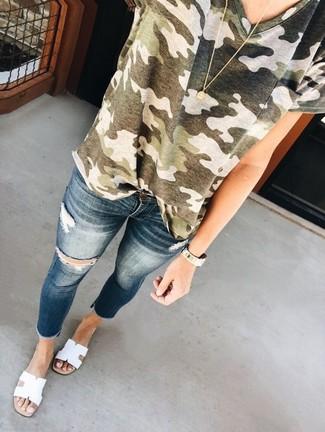 Cómo combinar: colgante dorado, sandalias planas de cuero blancas, vaqueros pitillo desgastados azul marino, camiseta con cuello circular de camuflaje verde oliva