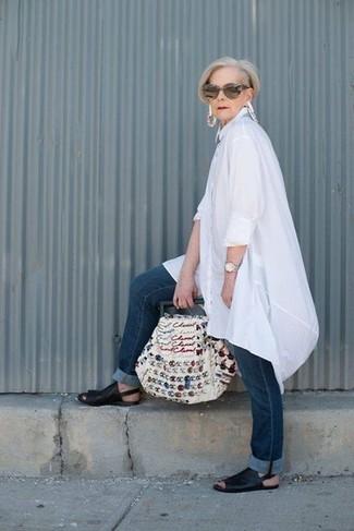 Moda para mujeres de 60 años estilo casual elegante: Este combo de una túnica de lino blanca y unos vaqueros azul marino te permitirá mantener un estilo cuando no estés trabajando limpio y simple. Sandalias planas de cuero negras resaltaran una combinación tan clásico.