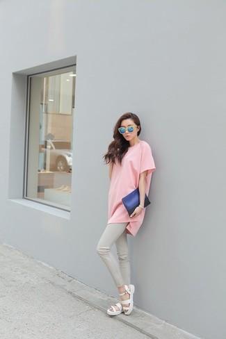Cómo combinar: cartera sobre de cuero azul, sandalias romanas blancas, pantalones pitillo grises, camiseta con cuello circular rosada