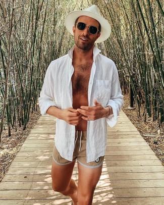 Cómo combinar: gafas de sol negras, sombrero de paja blanco, shorts de baño marrón claro, camisa de manga larga de lino blanca