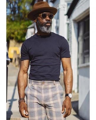 Cómo combinar: gafas de sol negras, sombrero de lana marrón, pantalón chino de tartán celeste, camiseta con cuello circular azul marino
