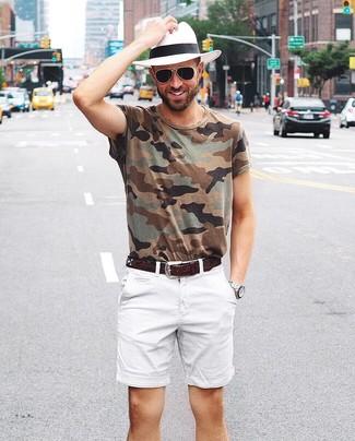 Cómo combinar: correa de cuero en marrón oscuro, sombrero de paja blanco, pantalones cortos blancos, camiseta con cuello circular de camuflaje verde oliva