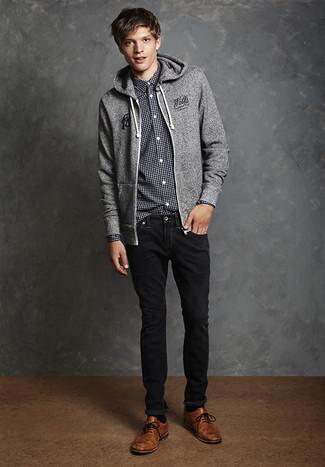 Look de moda: Sudadera con capucha gris, Camisa de manga larga de cuadro vichy en negro y blanco, Vaqueros negros, Zapatos brogue de cuero marrónes