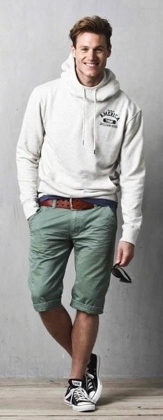 Cómo combinar: sudadera con capucha gris, camiseta con cuello circular azul marino, pantalones cortos verde oliva, tenis en negro y blanco