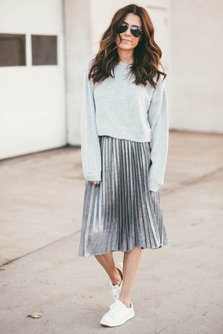 Cómo combinar: sudadera gris, falda midi plisada plateada, tenis blancos