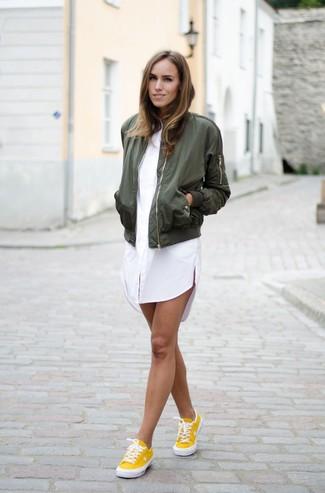 Cómo combinar: tenis amarillos, vestido camisa blanca, cazadora de aviador verde oliva