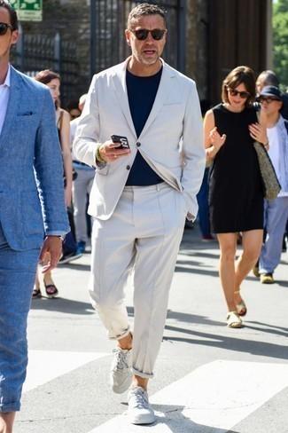 Combinar una camiseta: Una camiseta y un traje blanco son un look perfecto para ir a la moda y a la vez clásica. Tenis de cuero blancos son una opción buena para completar este atuendo.