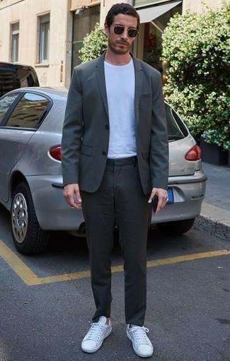 Combinar un traje en gris oscuro: Equípate un traje en gris oscuro junto a una camiseta con cuello circular blanca para crear un estilo informal elegante. ¿Quieres elegir un zapato informal? Opta por un par de tenis de cuero blancos para el día.