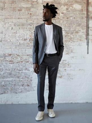 Combinar un traje en gris oscuro: Emparejar un traje en gris oscuro con una camiseta con cuello circular blanca es una opción inmejorable para un día en la oficina. Tenis de lona blancos añaden un toque de personalidad al look.