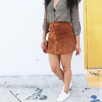 Cómo combinar: bolso bandolera de cuero marrón, tenis de lona blancos, falda con botones de ante marrón, camisa de vestir de rayas verticales en blanco y negro