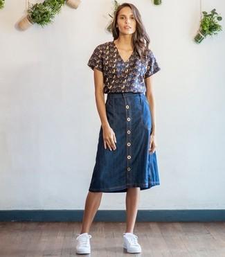 Cómo combinar: tenis blancos, falda con botones vaquera azul marino, blusa de manga corta estampada azul marino