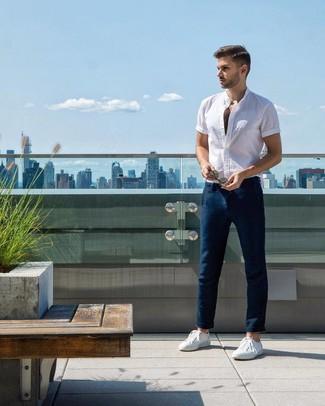 Cómo combinar: tenis blancos, pantalón chino azul marino, camisa de manga corta blanca
