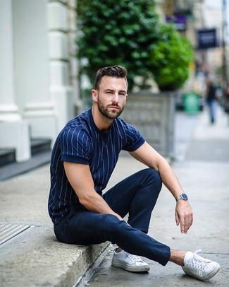 Cómo combinar: reloj plateado, tenis de lona blancos, pantalón chino azul marino, camiseta con cuello circular de rayas verticales azul marino