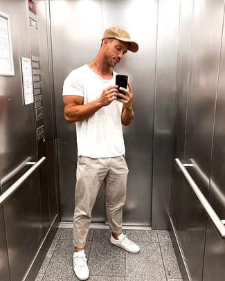 Cómo combinar: gorra de béisbol marrón claro, tenis blancos, pantalón chino en beige, camiseta con cuello circular blanca