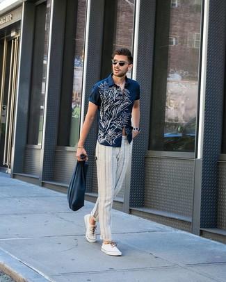 Cómo combinar: bolsa tote de lona azul marino, tenis de lona blancos, pantalón chino de rayas verticales en blanco y azul marino, camisa de manga corta con print de flores en azul marino y blanco