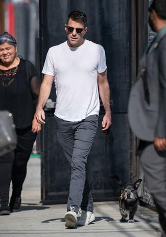 Cómo combinar: gafas de sol en marrón oscuro, tenis de cuero blancos, pantalón chino en gris oscuro, camiseta con cuello circular blanca