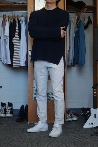 Outfits hombres estilo casuale: Opta por un jersey con cuello circular negro y un pantalón chino gris para una vestimenta cómoda que queda muy bien junta. ¿Quieres elegir un zapato informal? Opta por un par de tenis de cuero blancos para el día.
