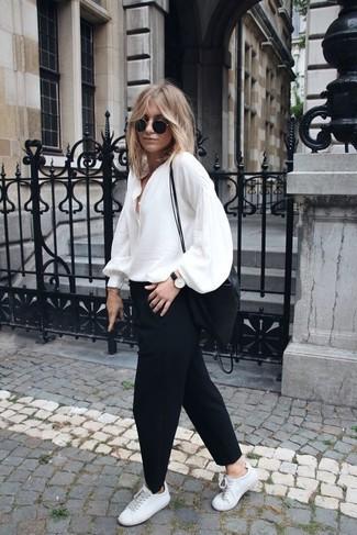 Cómo combinar: bolso bandolera de nylon negro, tenis de cuero blancos, pantalón chino negro, blusa de manga larga de seda blanca