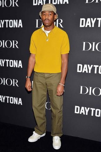 Cómo combinar: gorro de pescador en beige, tenis de cuero blancos, pantalón chino verde oliva, camisa polo mostaza