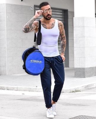 Cómo combinar: bolso baúl azul, tenis blancos, pantalón de chándal azul marino, camiseta sin mangas blanca