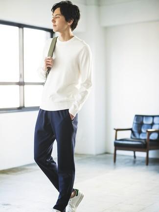 Cómo combinar: mochila verde oliva, tenis de cuero blancos, pantalón de chándal azul marino, jersey con cuello circular blanco