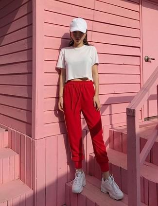 Cómo combinar: gorra inglesa blanca, tenis de cuero blancos, pantalón de chándal rojo, top corto blanco