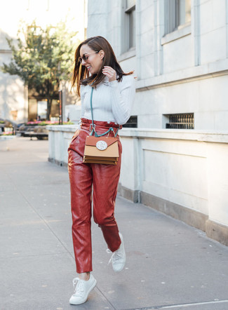Cómo combinar: bolso bandolera de cuero en tabaco, tenis de cuero blancos, pantalón de pinzas de cuero rojo, jersey de cuello alto celeste