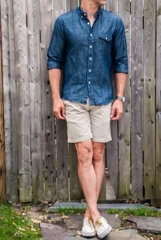 Combinar unos pantalones cortos en beige: Empareja una camisa de manga larga de cambray azul junto a unos pantalones cortos en beige para conseguir una apariencia relajada pero elegante. Tenis de lona blancos son una opción muy buena para completar este atuendo.