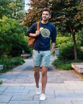 Cómo combinar: mochila en tabaco, tenis de lona blancos, pantalones cortos estampados en verde menta, sudadera estampada azul marino