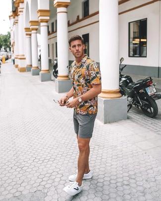 Cómo combinar: reloj de cuero marrón claro, tenis de cuero blancos, pantalones cortos grises, camisa de manga corta con print de flores amarilla