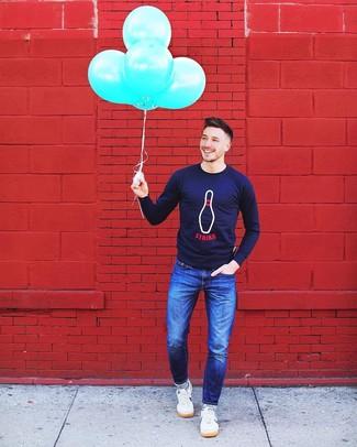 Cómo combinar: calcetines de rayas horizontales en azul marino y blanco, tenis blancos, vaqueros azules, jersey con cuello circular estampado azul marino