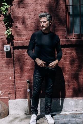 Outfits hombres estilo casuale: Intenta ponerse un jersey con cuello circular negro y unos vaqueros de cuero negros para cualquier sorpresa que haya en el día. Tenis blancos son una opción perfecta para complementar tu atuendo.