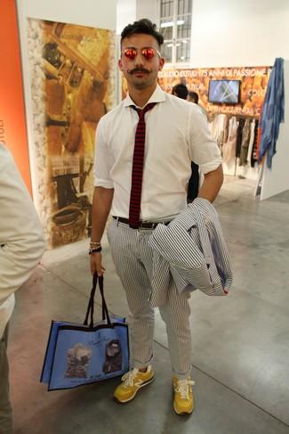 Cómo combinar: bolsa tote de lona estampada azul, tenis de ante amarillos, camisa de manga larga blanca, traje de seersucker de rayas verticales en azul marino y blanco