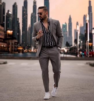 Cómo combinar: correa de cuero negra, tenis blancos, camisa de manga larga de rayas verticales en negro y blanco, traje gris