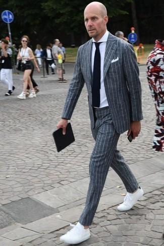 Combinar una corbata: Emparejar un traje de rayas verticales gris junto a una corbata es una opción perfecta para una apariencia clásica y refinada. Si no quieres vestir totalmente formal, elige un par de tenis blancos.