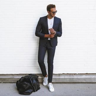Combinar un traje de rayas verticales negro: Intenta combinar un traje de rayas verticales negro junto a una camiseta con cuello circular blanca para las 8 horas. Mezcle diferentes estilos con tenis de cuero blancos.