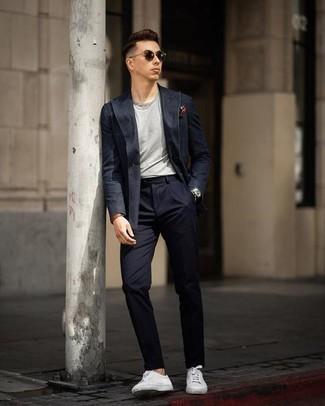 Combinar un traje azul marino: Empareja un traje azul marino junto a una camiseta con cuello circular gris para lograr un look de vestir pero no muy formal. Si no quieres vestir totalmente formal, opta por un par de tenis de cuero blancos.