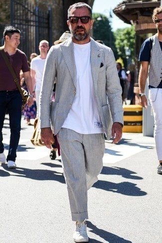 Combinar un traje de rayas verticales gris: Ponte un traje de rayas verticales gris y una camiseta con cuello circular blanca para un lindo look para el trabajo. Tenis de lona blancos añadirán un nuevo toque a un estilo que de lo contrario es clásico.