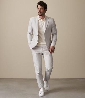 Cómo combinar: tenis de cuero blancos, camisa polo en beige, traje en beige