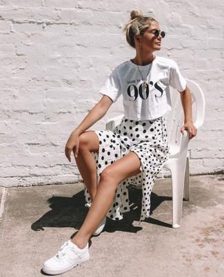 Cómo combinar: tenis de cuero blancos, falda midi a lunares en blanco y negro, camiseta con cuello circular estampada en blanco y negro