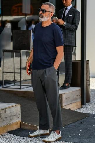 Cómo combinar: tenis de cuero blancos, pantalón chino en gris oscuro, camiseta con cuello circular azul marino