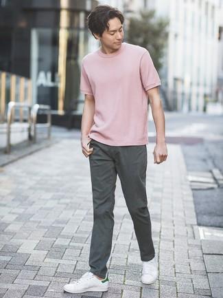 Cómo combinar: tenis de cuero blancos, pantalón chino en gris oscuro, camiseta con cuello circular rosada