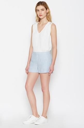 Cómo combinar: tenis de cuero blancos, pantalones cortos celestes, blusa sin mangas blanca