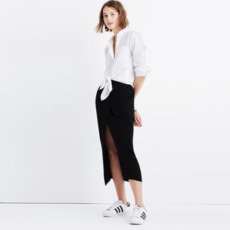 Cómo combinar: tenis de cuero en blanco y negro, falda midi con recorte negra, camisa de vestir blanca