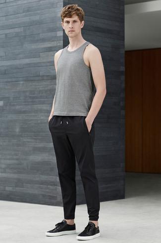 Cómo combinar: tenis de cuero negros, pantalón de chándal negro, camiseta sin mangas gris