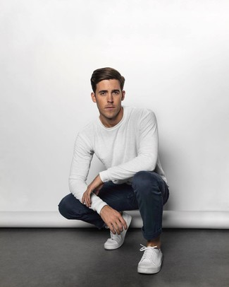 Cómo combinar: tenis de lona blancos, pantalón chino azul marino, camiseta de manga larga blanca